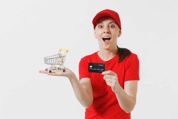 Entregadora de uniforme vermelho, isolado no fundo branco. correio feminino ou revendedor na tampa, t-shirt segurando o carrinho de empurrar do supermercado para compras, cartão de crédito. copie o espaço para anúncio.
