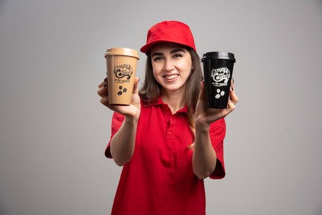Entregadora de uniforme vermelho segurando xícaras de café.