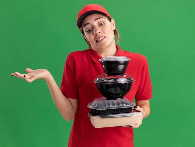 Entregadora jovem bonita confusa de uniforme segura e olha para os recipientes de comida na embalagem de alimentos no verde