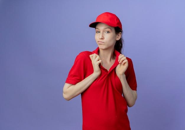 Entregadora jovem bonita e confiante, vestindo um uniforme vermelho e segurando o boné na gola da camiseta, isolada em um fundo roxo com espaço de cópia