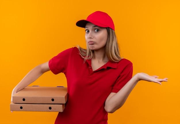 Entregadora jovem confusa, vestindo uniforme vermelho e boné, segurando uma caixa de pizza e espalhando a mão isolada na parede laranja