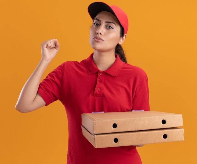 Entregadora jovem usando uniforme e boné segurando caixas de pizza levantando o punho isolado na parede laranja