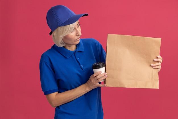 Entregadora loira de meia-idade impressionada com uniforme azul e boné segurando uma xícara de café de plástico e um pacote de papel, olhando para um pacote de papel isolado na parede rosa