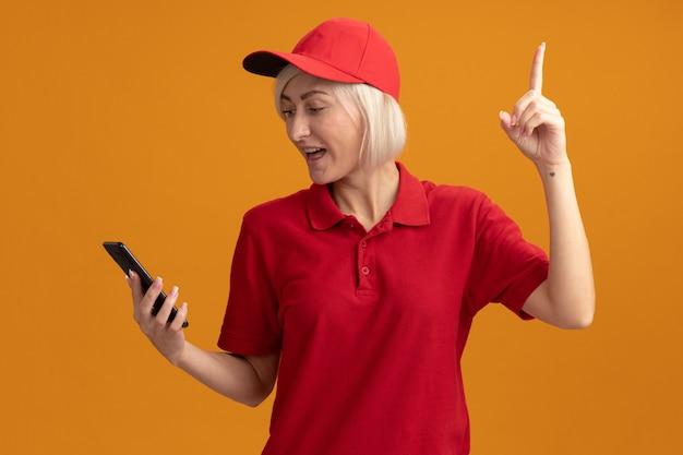 Entregadora loira de meia-idade impressionada com uniforme vermelho e boné segurando e olhando para o celular apontando para cima isolado na parede laranja