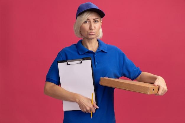 Entregadora loira de meia-idade, triste, com uniforme azul e boné segurando um pacote de pizza lápis para prancheta, isolado na parede rosa com espaço de cópia