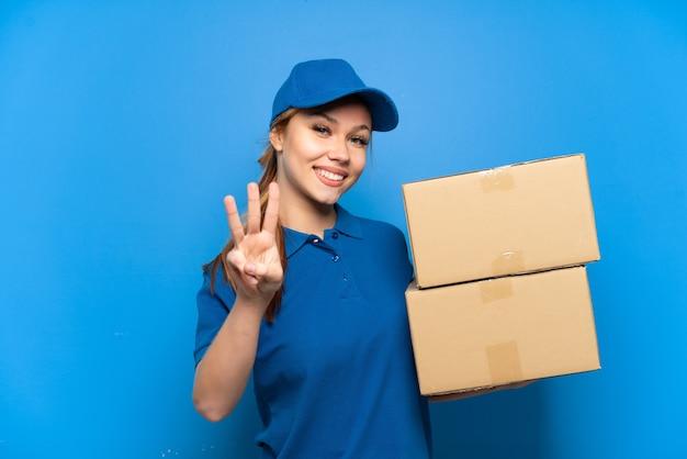 Entregadora na parede azul isolada feliz e contando três com os dedos