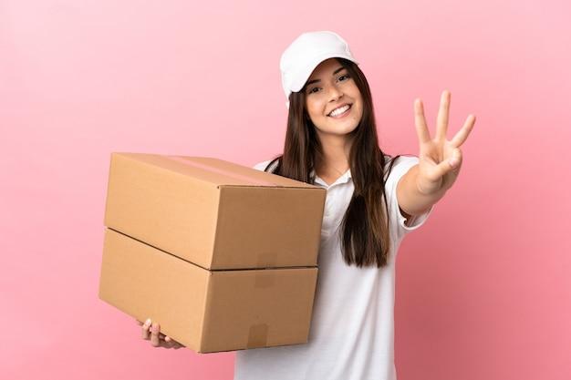 Entregadora na parede rosa isolada feliz e contando três com os dedos