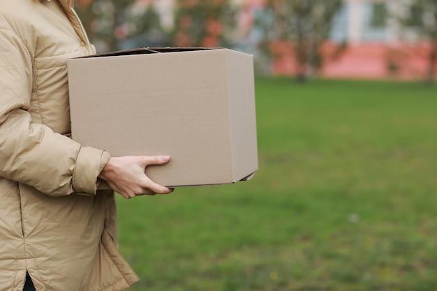 Entregadora recortada segurar caixa de papelão vazia ao ar livre em um fundo de complexo residencial.