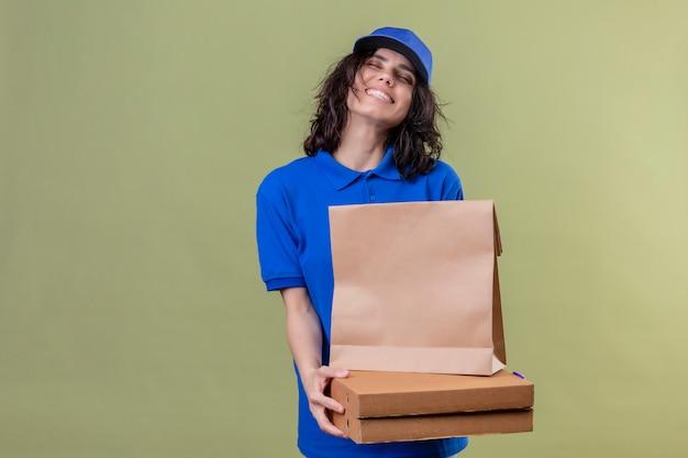 Entregadora satisfeita de uniforme azul, segurando caixas de pizza e pacote de papel com os olhos fechados, sorrindo com sorriso no rosto sobre parede de cor verde-oliva
