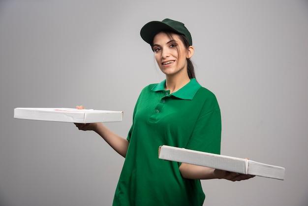 Entregadora segurando caixas de pizza