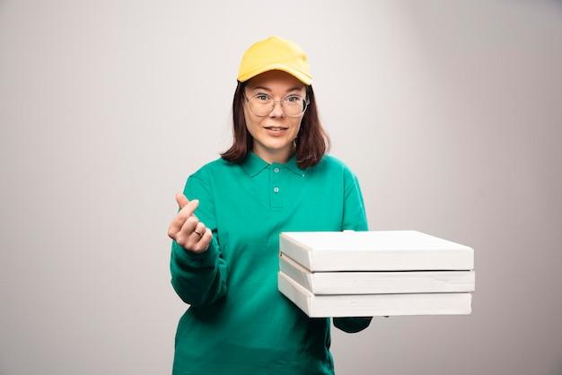 Entregadora segurando cartolinas de pizza em um branco. foto de alta qualidade