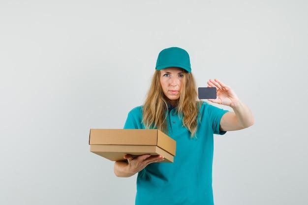 Entregadora segurando uma caixa de papelão e mostrando o cartão na camiseta, boné