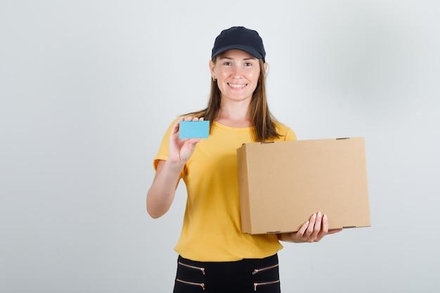 Entregadora segurando uma caixa de papelão e um cartão azul em uma camiseta, calça e boné e parecendo feliz