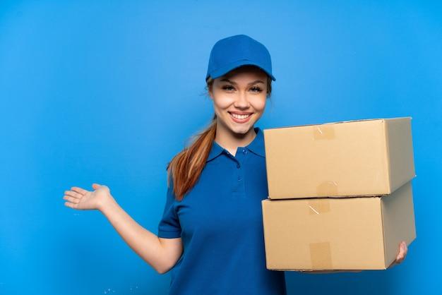 Entregadora sobre parede azul isolada estendendo as mãos para o lado para convidar para vir