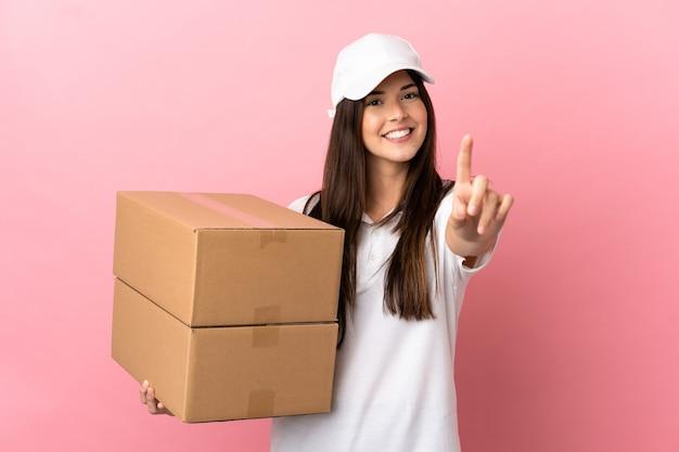 Entregadora sobre parede rosa isolada, mostrando e levantando um dedo