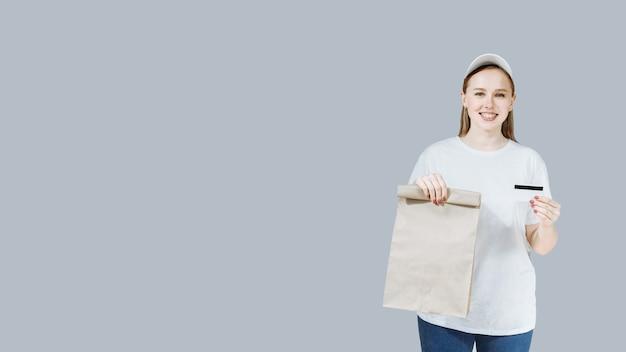 Entregadora sorridente segurando um pacote e um cartão de crédito em uniforme branco