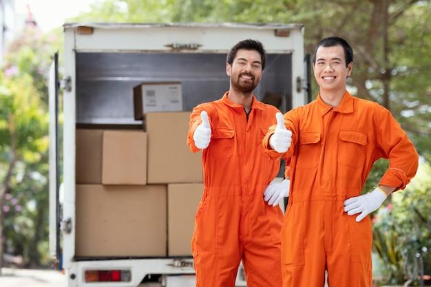 Entregadores mostrando sinal de ok perto do carro de entrega
