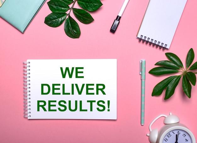 Entregamos resultados está escrito em verde em um bloco de notas branco sobre uma superfície rosa cercada por blocos de notas, canetas, despertador branco e folhas verdes. conceito educacional