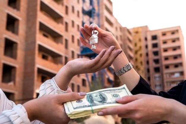 Entregando as chaves da casa entre o corretor de imóveis e o novo proprietário. conceito de venda