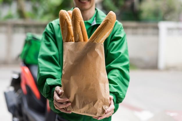 Entregar pão baguete ao cliente de motocicleta