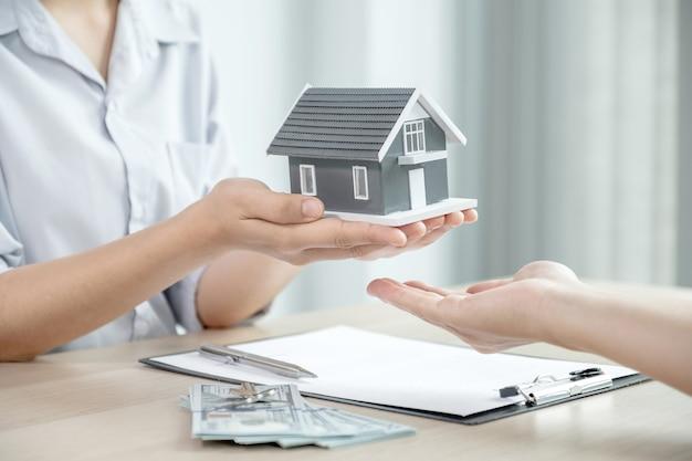 Entregar um corretor de imóveis, segurar o modelo da casa e explicar o contrato de negócios ou seguro da casa