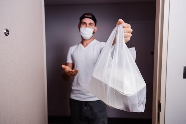 Entregar um homem segurando um saco plástico com comida