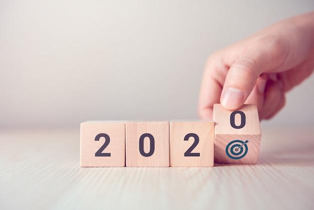 Entregue a aleta sobre os cubos de madeira de madeira com o ano novo 2020 e o conceito do ícone do objetivo.