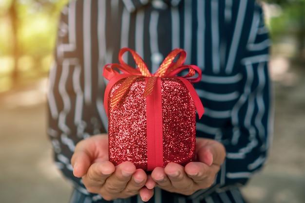 Entregue a caixa de presente da preensão a alguém no fundo verde da natureza do bokeh. conceito de feriado de comemoração.