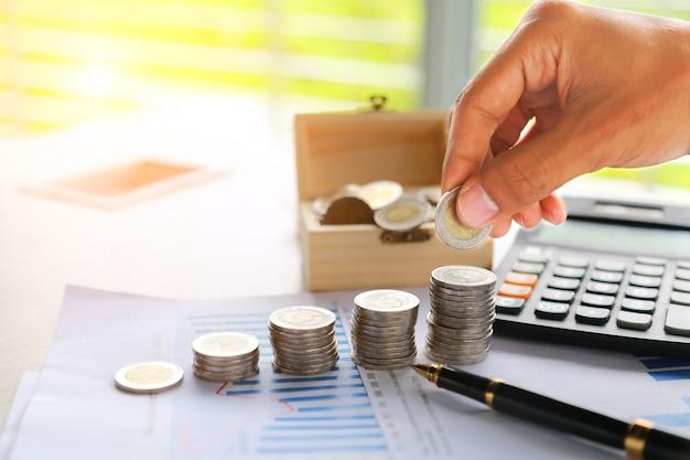 Entregue a colocação de moedas do dinheiro empilhe no dinheiro da economia e no conceito crescente do negócio.