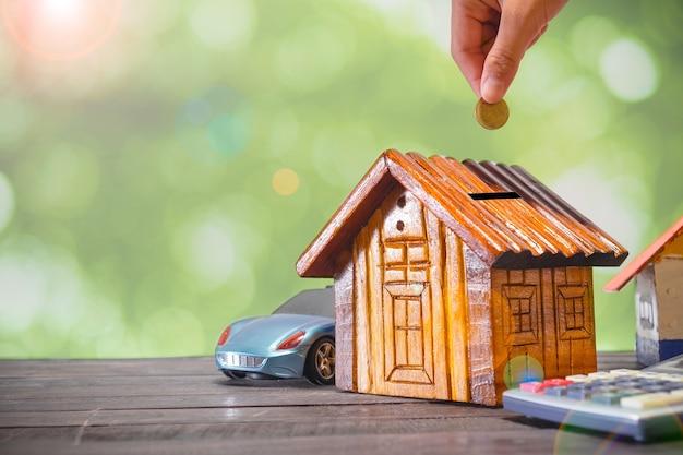 Entregue a colocação de moedas douradas no modelo de madeira da casa do dinheiro. conceito de plano de poupança para habitação