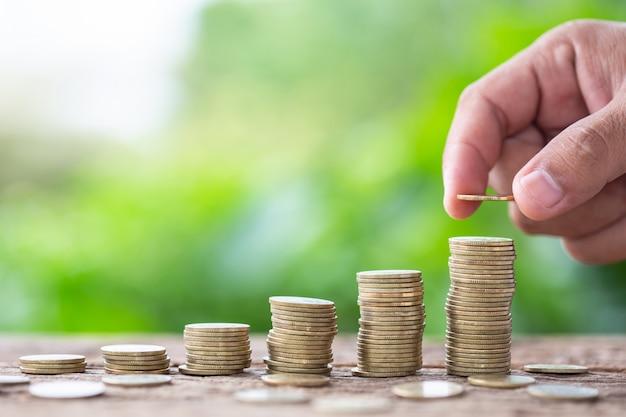 Entregue a colocação de moedas na pilha na prancha de madeira com fundo verde do borrão. conceito de poupança