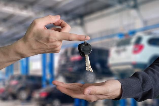 Entregue a entrega de chaves do carro com o dedo e a mão que recebe no centro de serviço da garagem