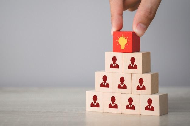 Entregue a escolha do cubo de madeira com lâmpada de ícone e símbolo humano, idéia criativa e conceito de inovação.