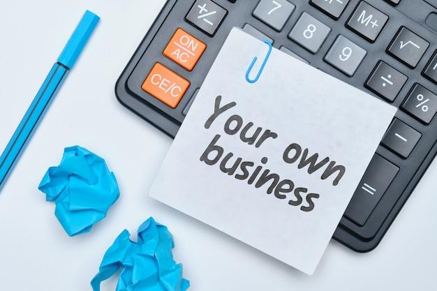 Entregue a escrita em um caderno seu próprio negócio em um fundo branco com uma calculadora.
