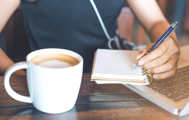 Entregue a mulher de negócio que usa o portátil e escrevendo no bloco de notas.