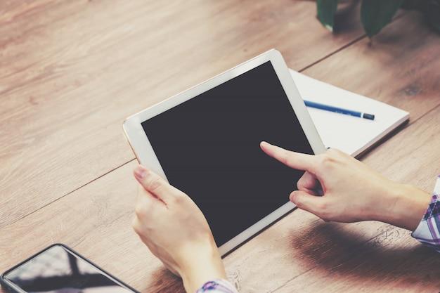 Entregue a mulher que usa o tablet pc na tabela de madeira com o vintage tonificado.