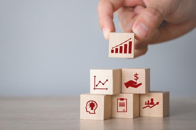 Entregue a organização do bloco de madeira que empilha com seta e negócio do ícone, alvejando o conceito do negócio.