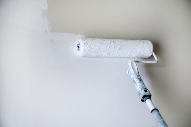 Entregue a parede da pintura com rolo de pintura, cor pastel. apartamento renovação, reparação, construção e conceito de casa. copie o espaço. ferramentas para pintar paredes.