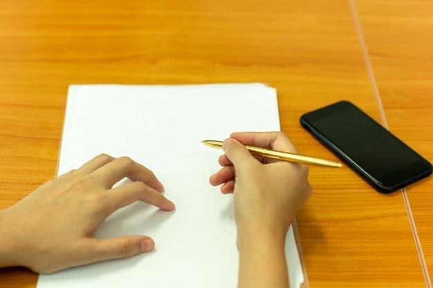 Entregue a pena de terra arrendada a tomar notas no documento na sala de reunião da conferência.