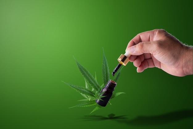 Entregue a pipeta da terra arrendada do óleo do cannabis sobre um frasco da fórmula cbd thc.