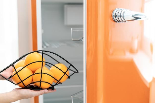 Entregue a porta aberta da geladeira na cozinha. laranja na mão.