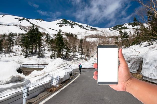 Entregue a posse o telefone celular com uma estrada da montanha dos cumes de japão da parede da neve, japão.