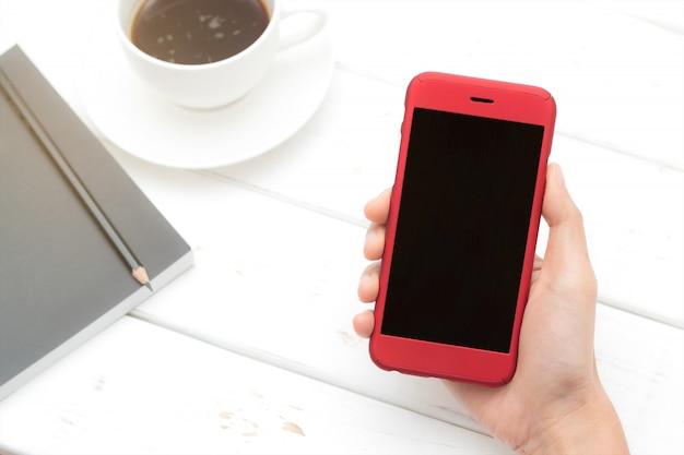 Entregue a preensão a tela preta do telefone com efeito do filtro do alargamento. esta imagem tem um traçado de recorte na seção de tela.