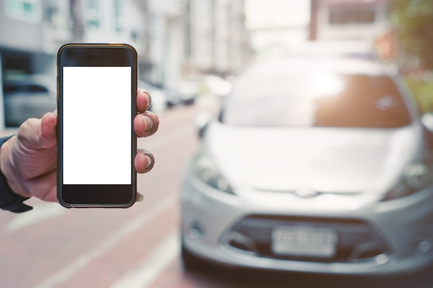 Entregue a tela em branco do smartphone móvel com o veículo do carro para o conceito de plano de fundo do app do telefone de movimentação inteligente.