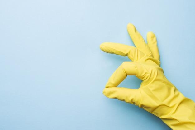 Entregue em luvas amarelas para limpar no fundo azul.