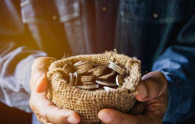 Entregue guardar moedas de ouro do dinheiro com planta à disposição para o conceito financeiro e salvar do dinheiro.