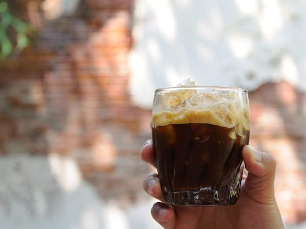Entregue guardar um vidro do café congelado por horas de verão com o fundo da parede de tijolo velha.