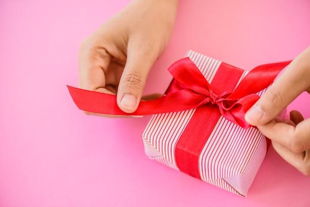 Entregue guardar uma caixa de presente vermelha no fundo cor-de-rosa conceito do natal e do ano novo.