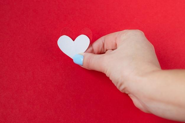 Entregue guardarar um coração branco em um fundo vermelho. plano de fundo para o dia dos namorados