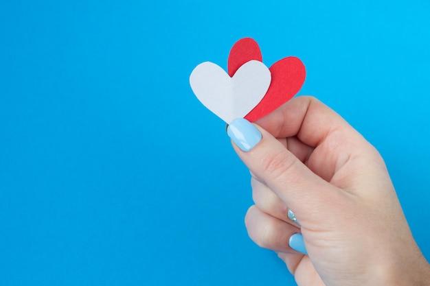 Entregue guardarar um coração vermelho e branco em um fundo azul. plano de fundo para o dia dos namorados